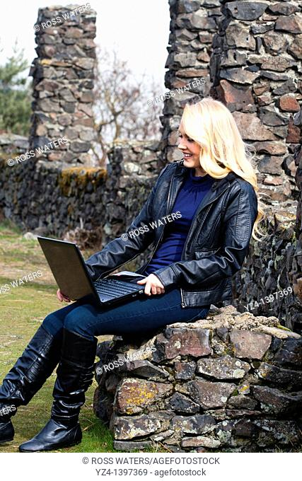 A young woman outdoors with a laptop