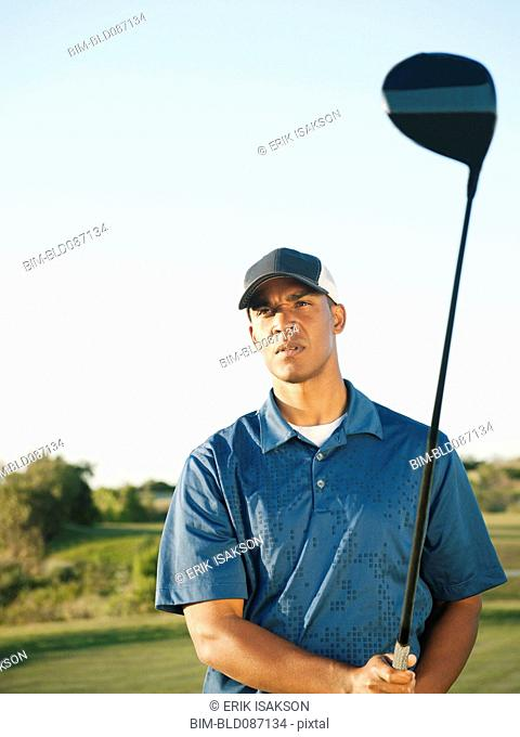 Black golfer holding golf club