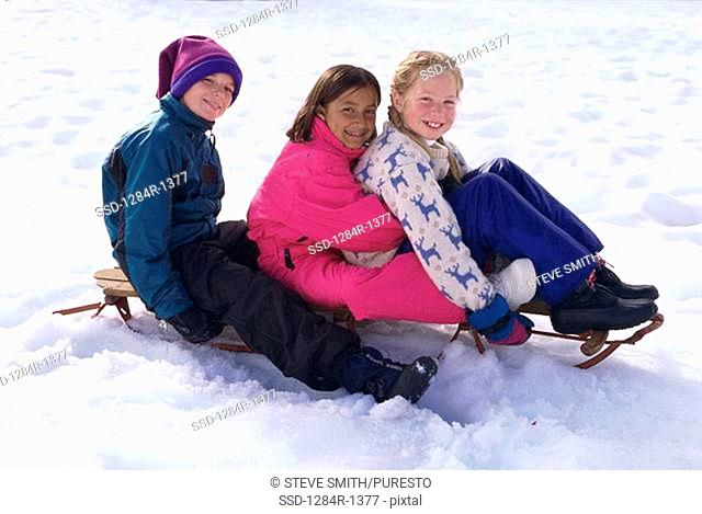 Portrait of a boy and two girls sitting on a sled