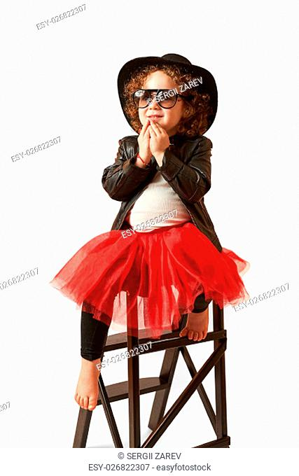 Little girl with black hat sitting on a high stool and thinking