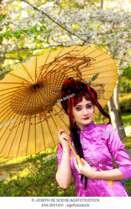 A 20 year old woman in Asian themed hair and make up, holding a parasol in a garden setting. Birmingham, Alabama, USA