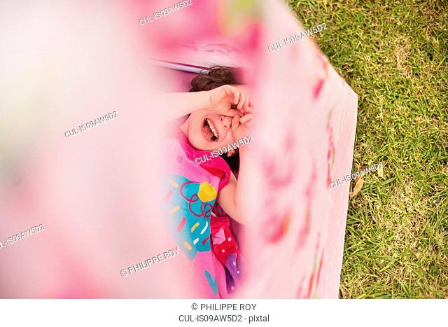 Overhead view of girl in teepee, hands covering eyes smiling