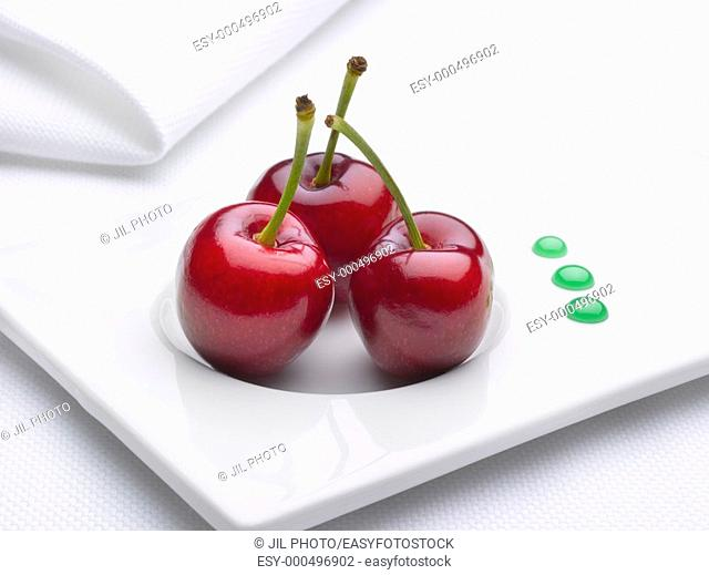 Three cherries with drops of mint syrup