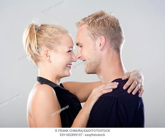 young happy couple embracing, smiling - isolated on light gray