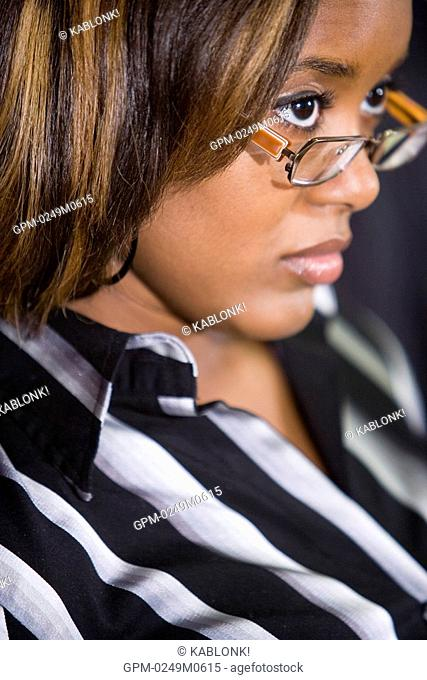 Headshot of serious young African woman wearing glasses looking intently