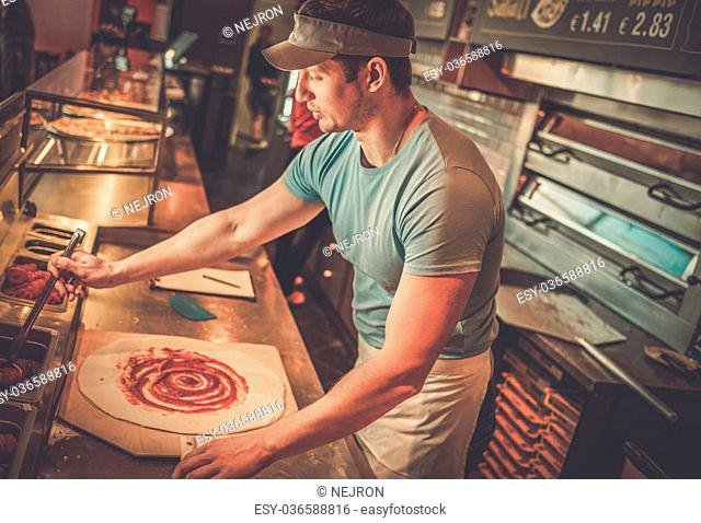 Handsome pizzaiolo making pizza at kitchen in pizzeria