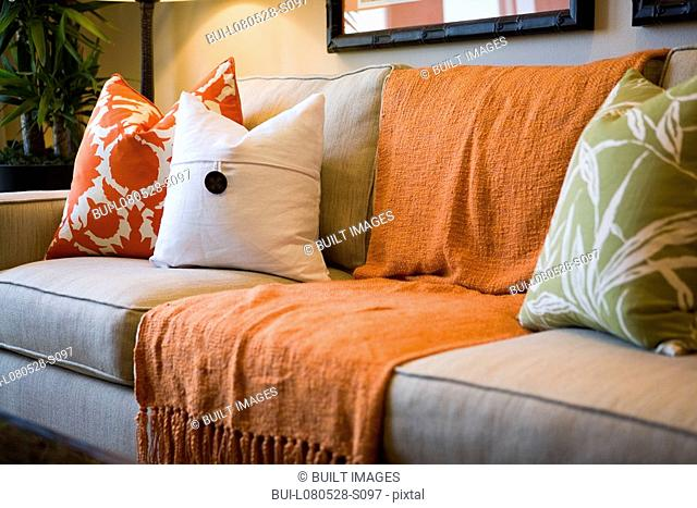 Comfortable sofa with orange throw blanket and decorative pillows