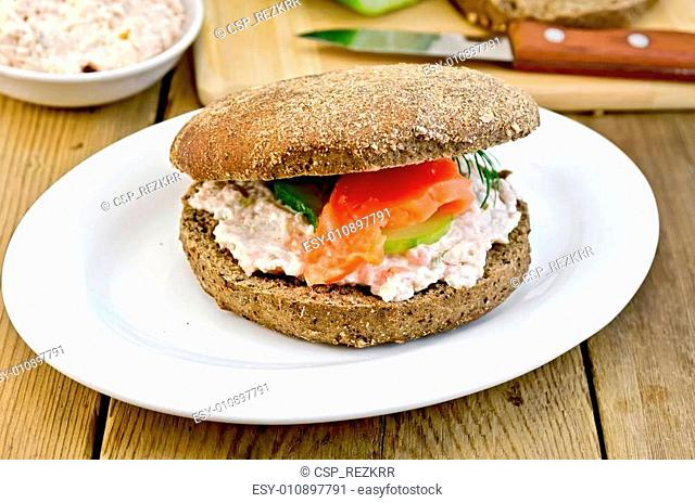 Sandwich with cream and salmon on a board with a knife