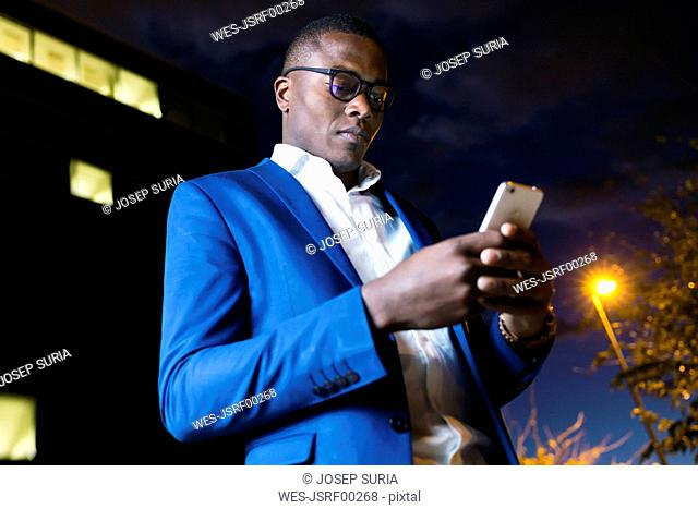Young businessman wearing blue suit jacket and using smartphone at night