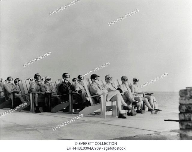 VIPs view the DOG shot, an 81 kiloton atomic detonation wearing safety goggles. They are sitting on Adirondack chair of the Officers Beach Club patio on...