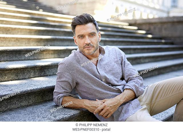 Portrait of serious mature man sitting on stairs