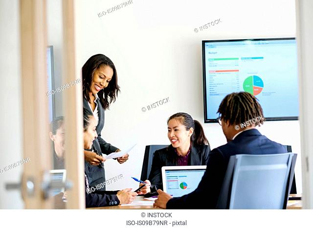 Businessman and businesswomen, sitting in office, having discussion, looking at data