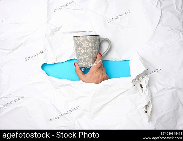 female hand holding a ceramic mug on a background of white torn paper, time to drink coffee and relax