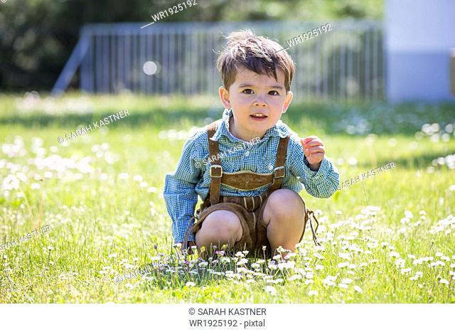 Little boy with leather pants picking flowers