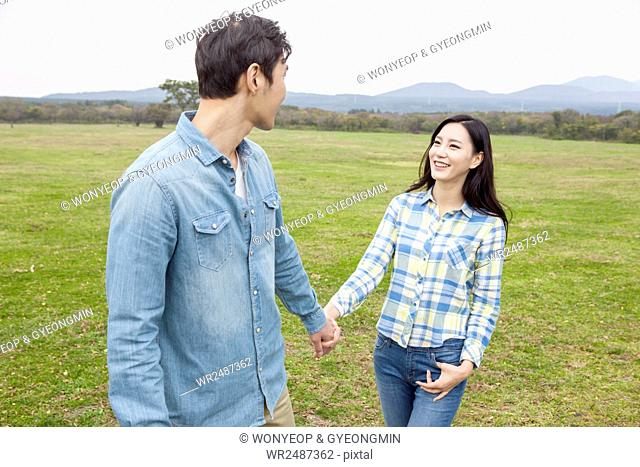 Young smiling couple walking hand in hand face to face on grassland