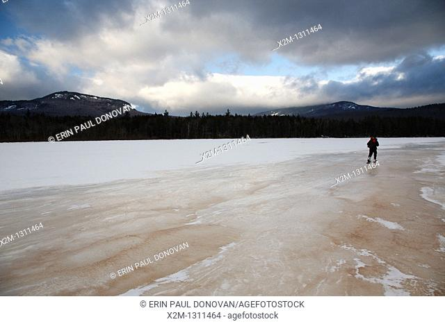Hiker snowshoeing on the edge of Church Pond in the White Mountains, New Hampshire USA  This area was part of the Swift River Railroad era