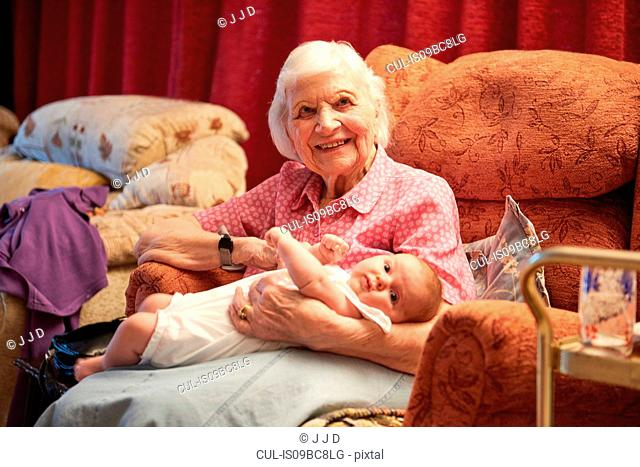 Senior woman cradling baby great granddaughter on armchair, portrait