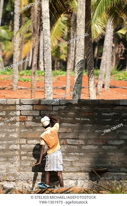 Man building a wall near Varkala Beach,Kerala,India