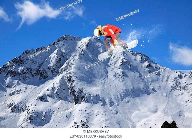 Snowboard rider jumping on snowy mountains. Extreme snowboard freeride sport