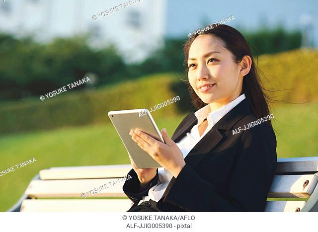 Young Japanese businesswoman with tablet by a river downtown Tokyo