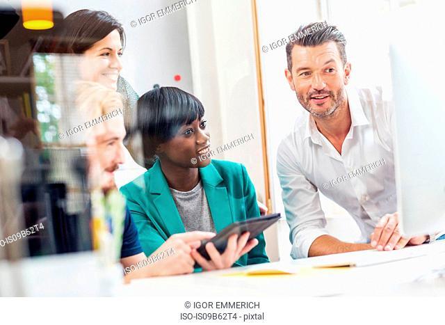 Designer team looking at computer in creative studio