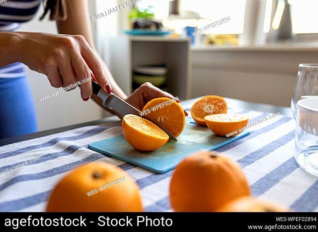 Woman slicing fresh oranges for freshly squeezed orange juice