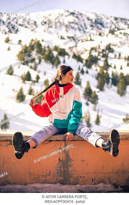Spain, Benasque, teenage girl sitting on a wall in winter