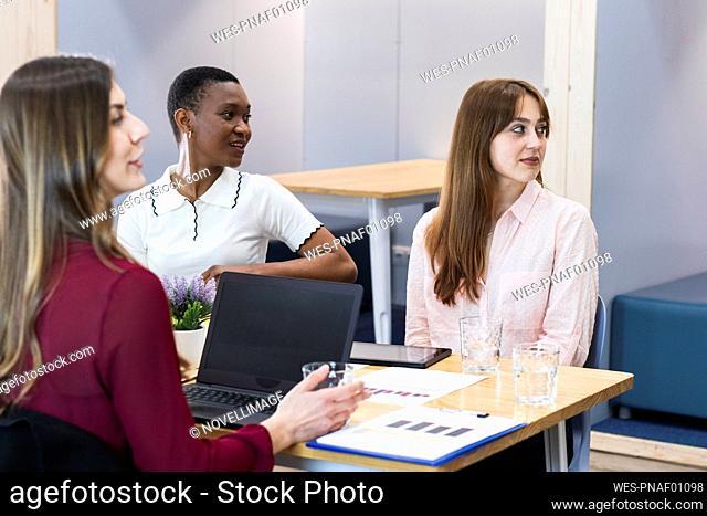 Female entrepreneurs looking away in meeting at office