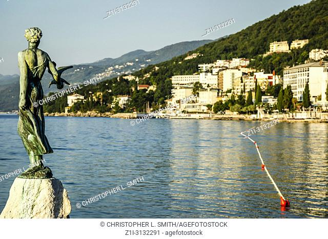 Bronze sculpture of Maiden with Seagull on background a sea and city of Opatija, Croatia