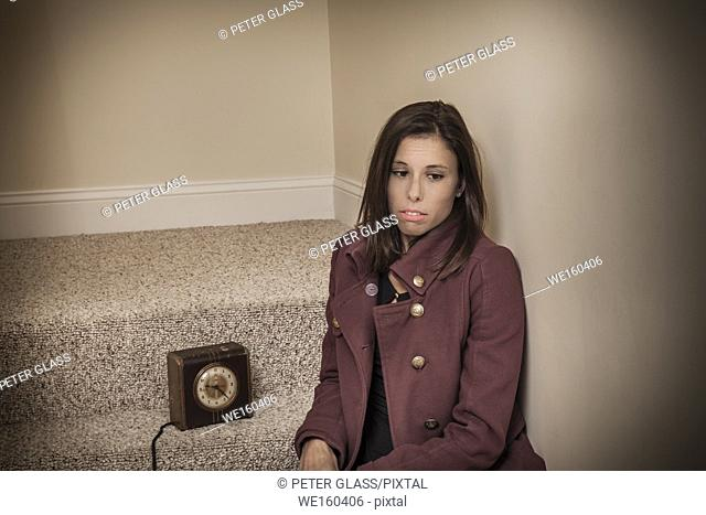 Young woman sitting on stairs next to an old fashioned clock