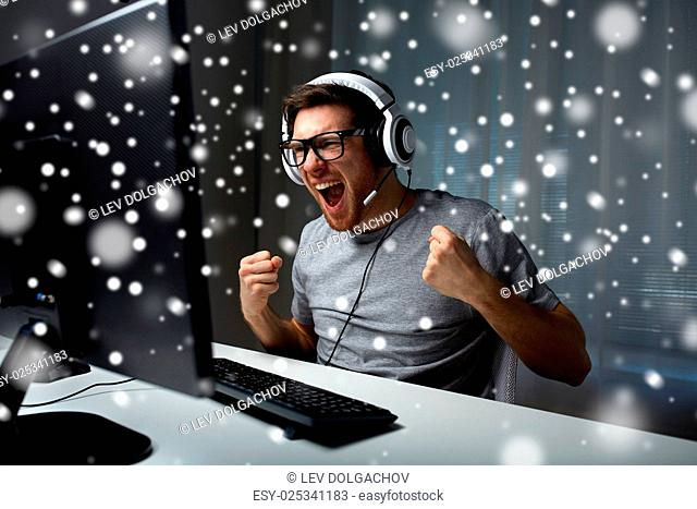 technology, gaming, entertainment, let's play and people concept - man in eyeglasses with headset playing and winning computer game at home and streaming...