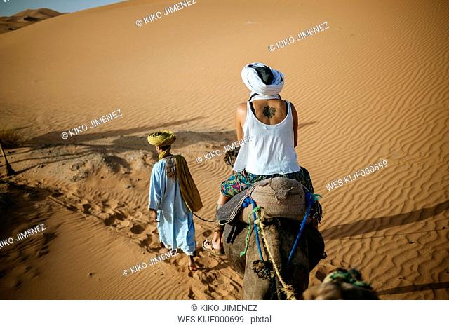 Woman riding a camel in the desert with Berber guide