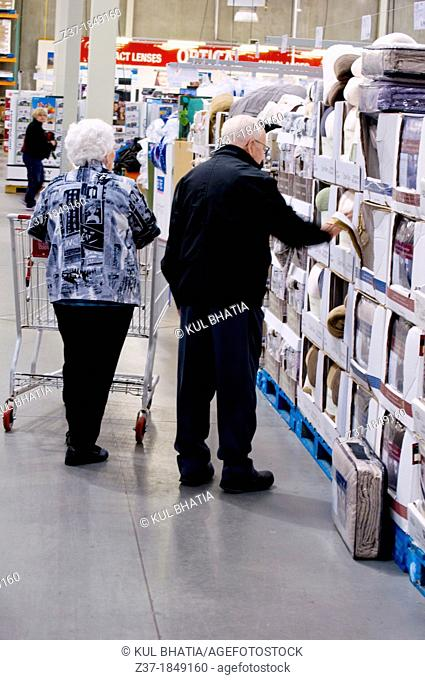 Two seniors check the shelves in a store, Ontario, Canada