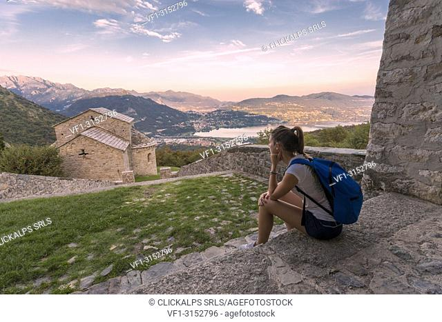 Woman sightseeing at the abbey of San Pietro al Monte, an ancient monastic complex of Romanesque style in the town of Civate, Lecco province, Lombardy, italy
