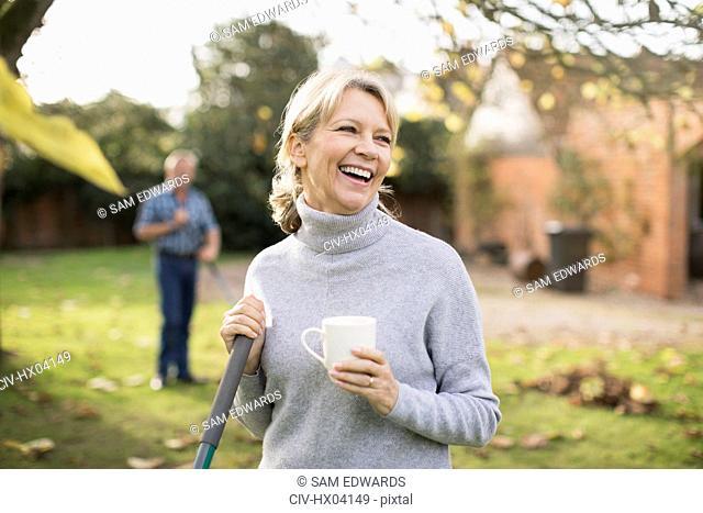 Happy mature woman drinking coffee and raking autumn leaves in backyard