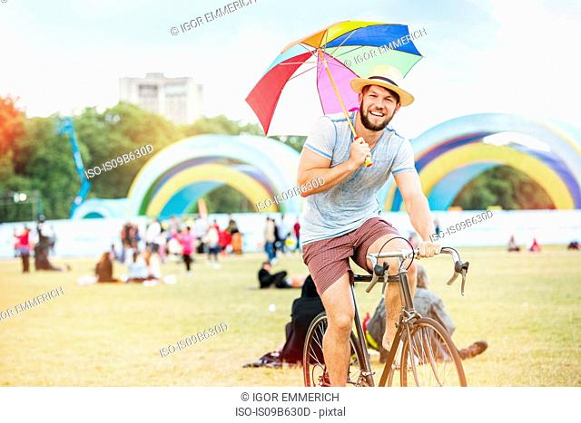 Man with umbrella riding bicycle at festival