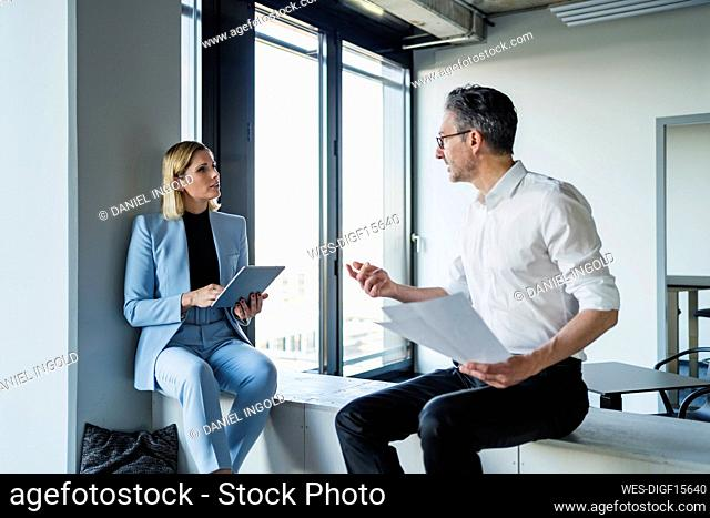 Mature businessman discussing with female colleague while sitting on furniture in office