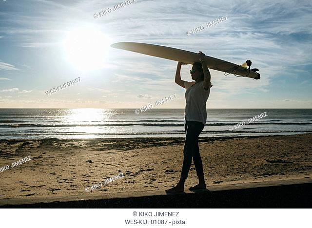 Young woman carrying surfboard head on the beach