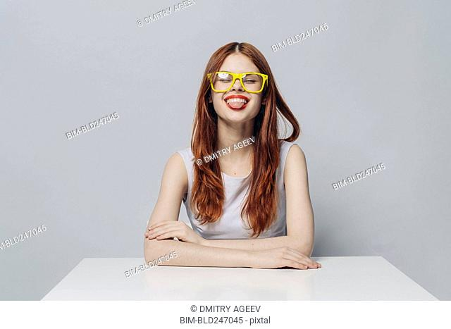 Caucasian woman sitting at table with tongue out