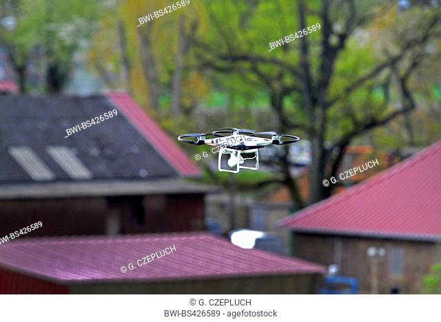 drone with camera flying above roofs, Germany