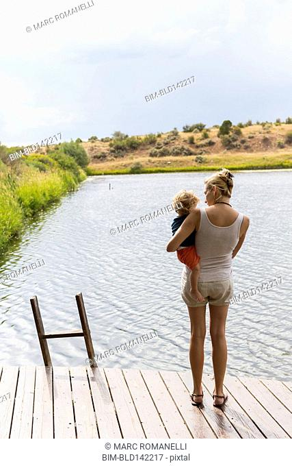 Caucasian mother holding baby son on wooden deck near lake