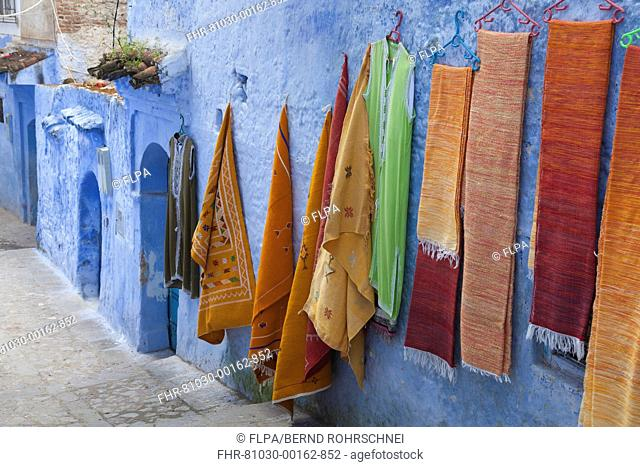 Blue houses and textiles for sale in alley of city, Chefchaouen, Morocco, april