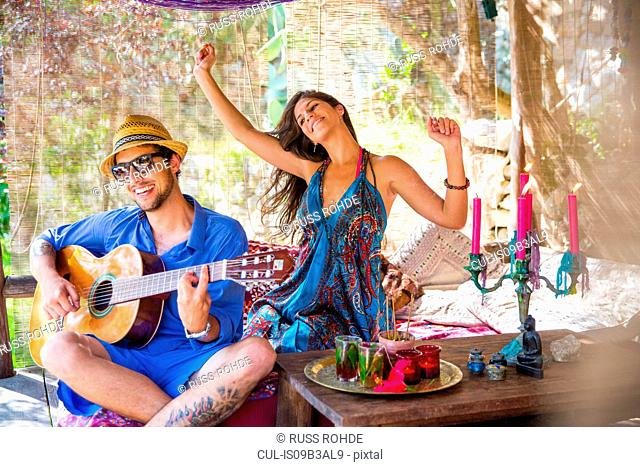 Young couple playing guitar smiling, dancing