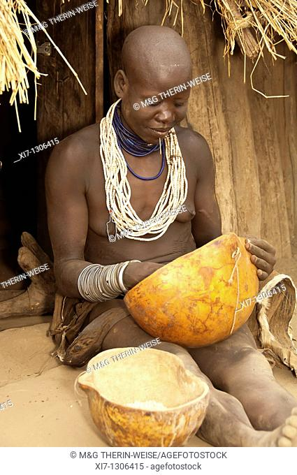 Karo woman with lots of colorful necklaces, lip piercing and calabashes in front of her hut, Omo river valley, Southern Ethiopia