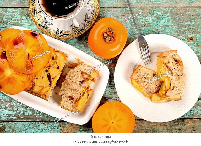 Homemade persimmon cake with fresh persimmons overhead view