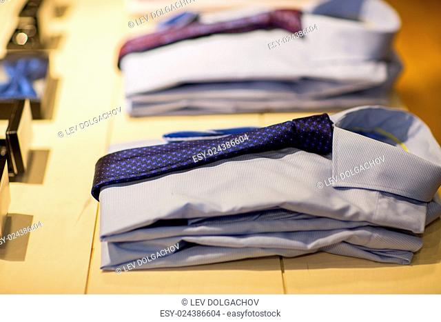 sale, shopping, male fashion, style and wear concept - close up of shirts with ties at clothing store