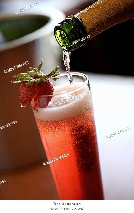 Champagne being poured into a glass garnished with a strawberry. A fruit cocktail