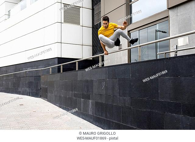 Young man jumping over railing