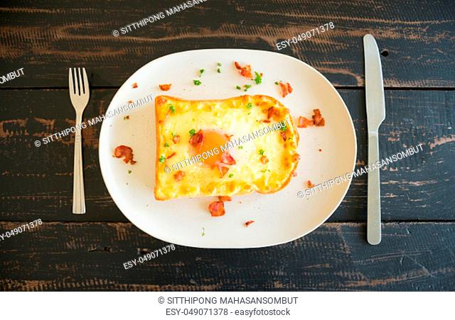 Egg Yolk Bacon Ham Cheese Toast and Coriander. Breakfast egg yolk bacon ham cheese with bread toast with coriander on top for food and drink category