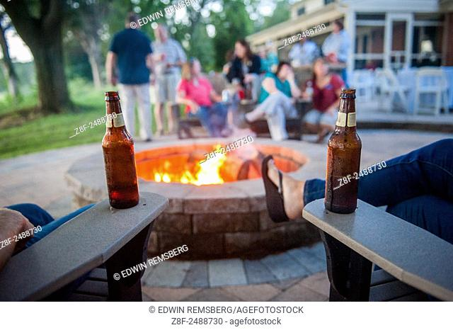 People at a party in the backyard, around a fire pit. Beer bottles can be seen on the arms of the lawn furniture. Salisbury, Maryland, USA